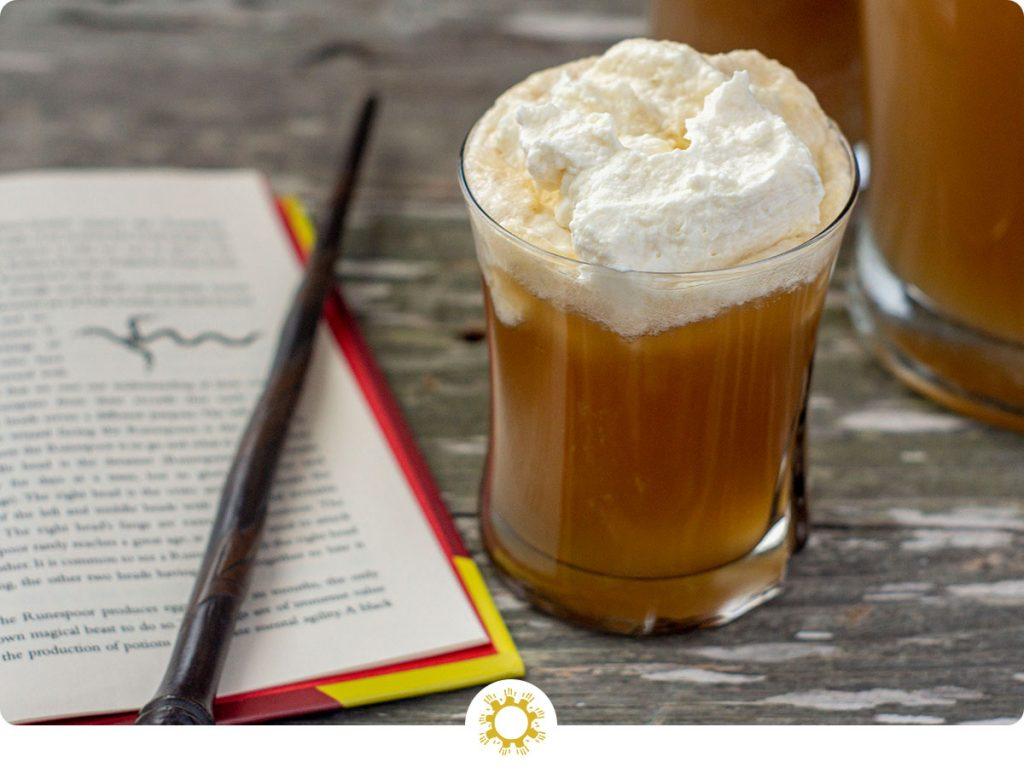 Glass of Butterbeer topped with whipped topping next to an open book and a magic wand with a pitcher of Butterbeer in the background all on a wooden surface (with logo overlay)