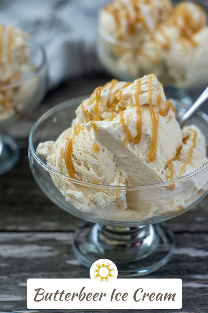 3 glass dessert dishes filled with butterbeer ice cream drizzled with butterscotch syrup with a spoon in the ice cream with a white and brown towel behind all on a wooden surface (vertical with title overlay)