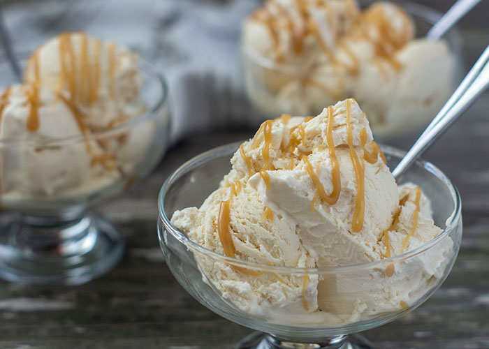 3 glass dessert dishes filled with butterbeer ice cream drizzled with butterscotch syrup with a spoon in the ice cream with a white and brown towel behind all on a wooden surface