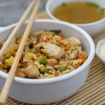 Chicken fried rice in a white bowl with wooden chopsticks across the top next to a bowl of clear onion soup and a small dish of white sauce on a bamboo placemat