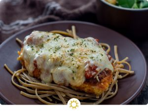 Chicken parmesan on top of a bed of noodles on a round brown plate with a white bowl of salad and a brown and white towel behind all on a wooden surface (with logo overlay)
