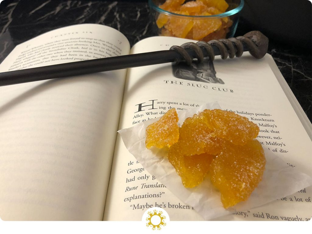 Crystallized Pineapple on a piece of wax paper sitting on an open Harry Potter book with a wand on top with a glass bowl of crystallized pineapple behind the book all on a black and white marble surface (with logo overlay)