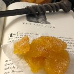 Crystallized Pineapple on a piece of wax paper sitting on an open Harry Potter book with a wand on top with a glass bowl of crystallized pineapple behind the book all on a black and white marble surface (with large title overlay)