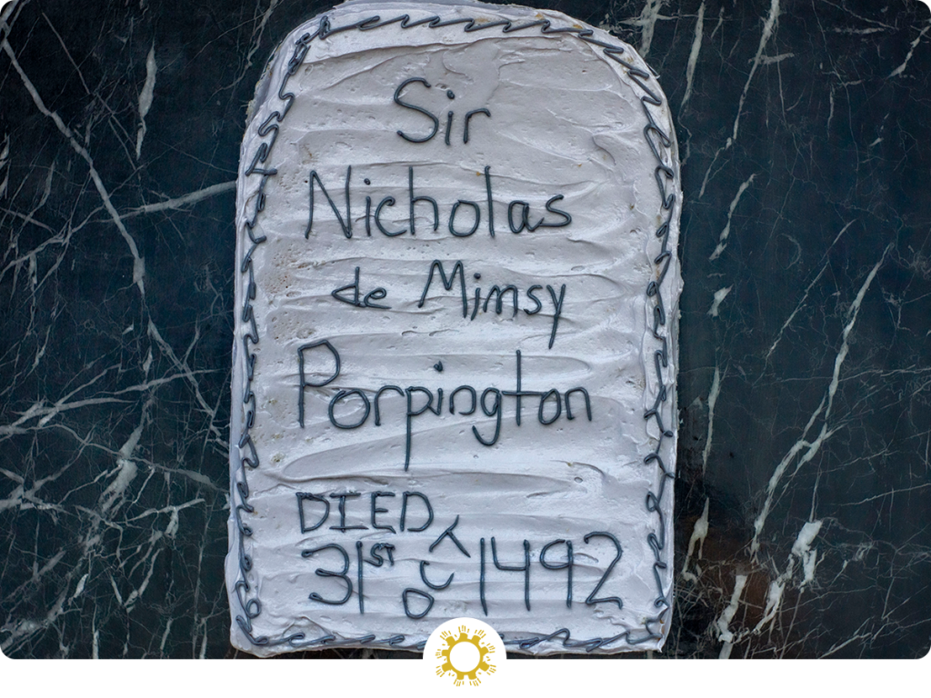 Nearly Headless Nick's Deathday Cake: rectangular cake with rounded tops covered in grey frosting with dark writing on a dark granite surface (with logo overlay)