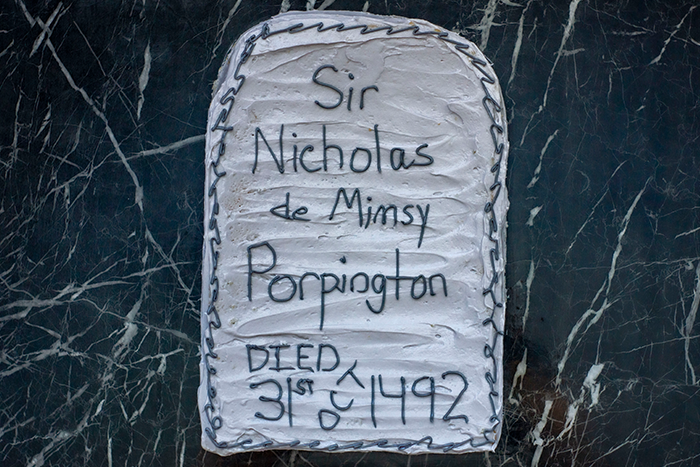 Nearly Headless Nick's Deathday Cake: rectangular cake with rounded tops covered in grey frosting with dark writing on a dark granite surface