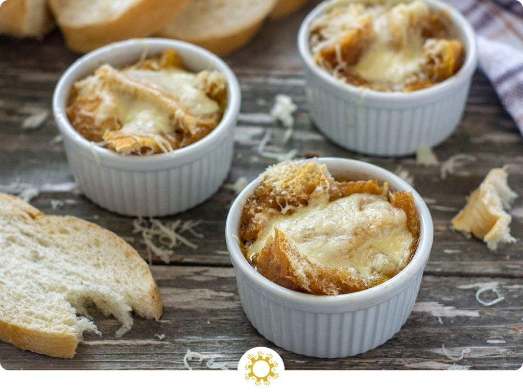 3 small white ramekins with cooked french onion soup on a wooden surface with shredded cheese and chunks of bread around them with sliced bread and a towel in the background (with logo overlay)