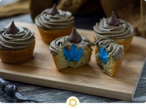 Sorting hat cupcakes with one cut in half showing blue frosting inside on a bamboo board with the sorting hat behind and a magic wand in front all on a wooden surface (with logo overlay)