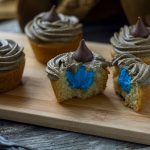 Sorting hat cupcakes with one cut in half showing blue frosting inside on a bamboo board with the sorting hat behind and a magic wand in front all on a wooden surface