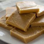 Treacle fudge piled on a white plate on top of a tan placemat on a wooden surface