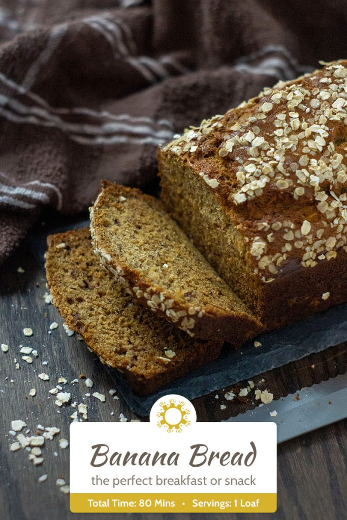 Banana Bread covered with oats on a slate serving plate next to a brown towel and a bread knife on a wooden surface (vertical with title overlay)
