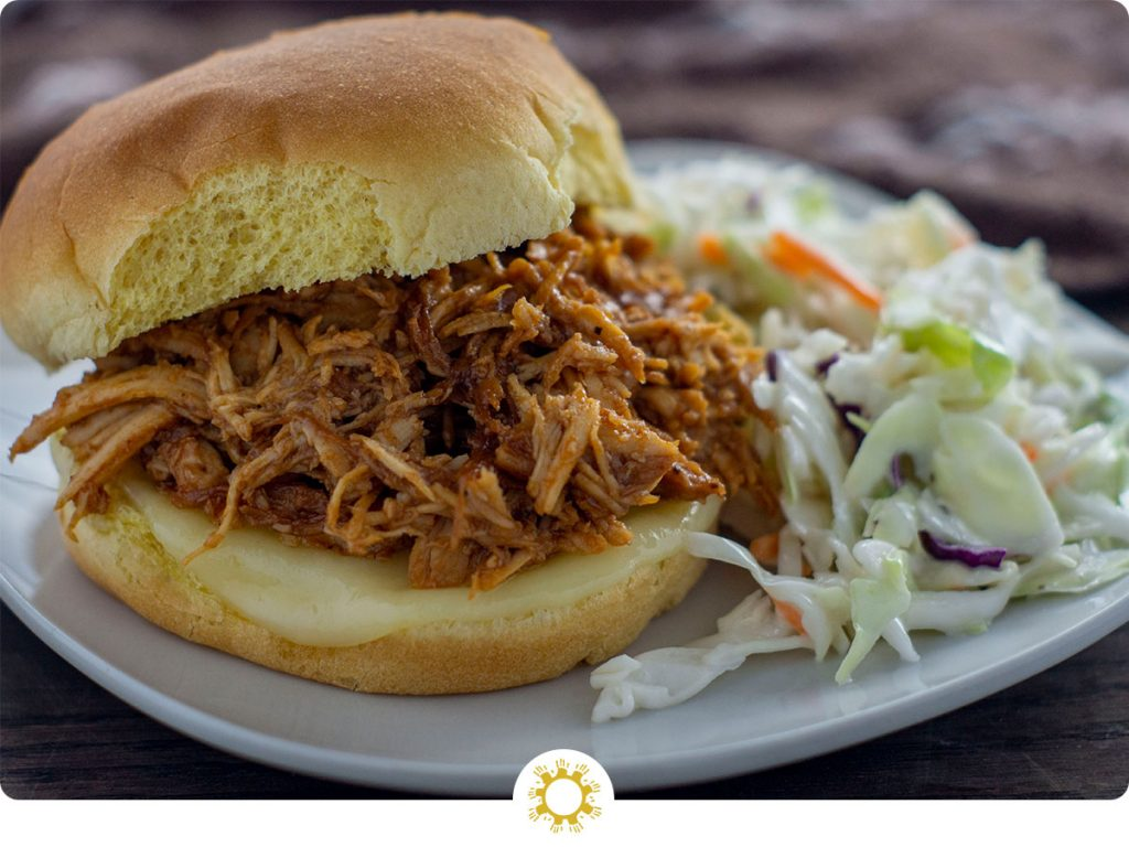 Shredded bbq chicken with melted cheese on a hamburger bun with coleslaw on a white plate with a brown towel behind all on a wooden surface (with logo overlay)
