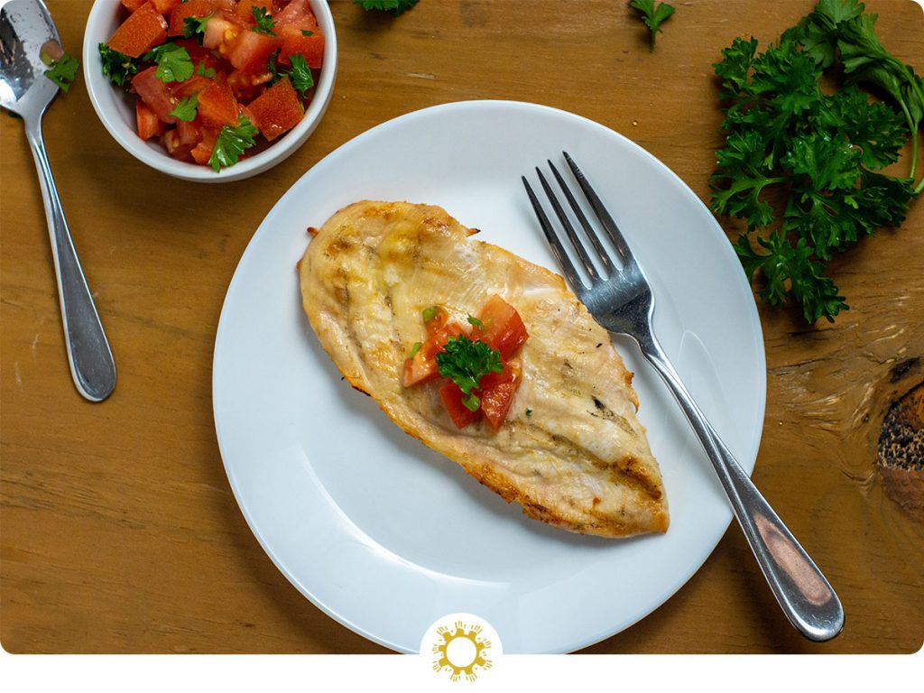 Grilled chicken topped with chopped tomatoes and cilantro next to a fork on a round white plate with a bunch of cilantro to the top right and a bowl of tomato salsa to the top left with a spoon all on a wooden surface (with logo overlay)