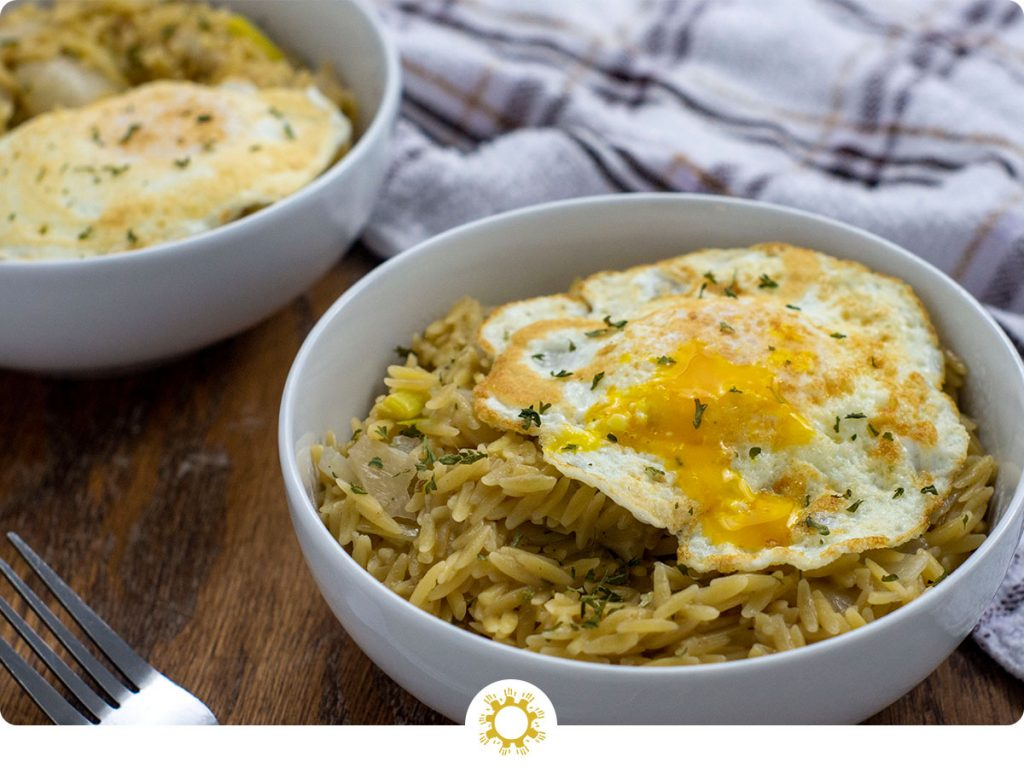 Leek orzo with fried egg garnished with parsley in two round white bowls with a stainless steel fork and a white and brown towel all on a wooden surface (with logo overlay)
