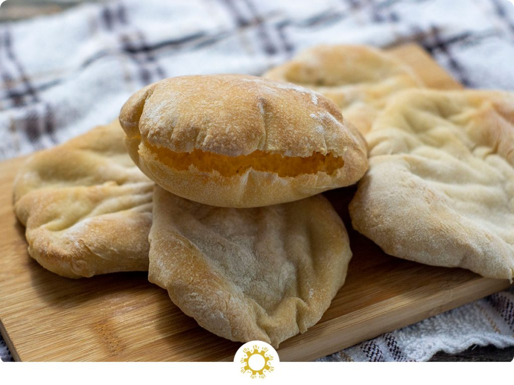 Pita bread pockets in a pile with the top one opened on top of a bamboo serving board on a white and brown towel all on a wooden surface (with logo overlay)