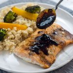 Woman's hand holding a spoon with soy-molasses glaze dripping onto a fillet of cooked salmon next to a bed of rice with roasted yellow bell pepper and broccoli on a round white and grey marbled plate on top of a grey placemat on a white and grey marbled surface