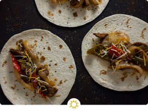 Overhead view of three flour tortillas topped with cooked fajita steak topped with cooked onions, green bell peppers, red bell peppers, and shredded cheese all on a wooden surface (with logo overlay)