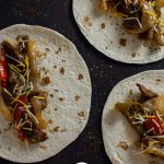Overhead view of three flour tortillas topped with cooked fajita steak topped with cooked onions, green bell peppers, red bell peppers, and shredded cheese all on a wooden surface (vertical with title overlay)