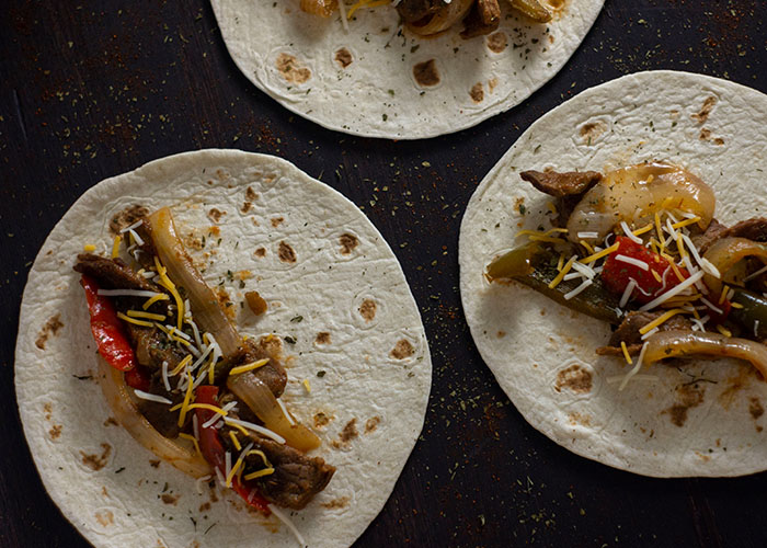 Overhead view of three flour tortillas topped with cooked fajita steak topped with cooked onions, green bell peppers, red bell peppers, and shredded cheese all on a wooden surface