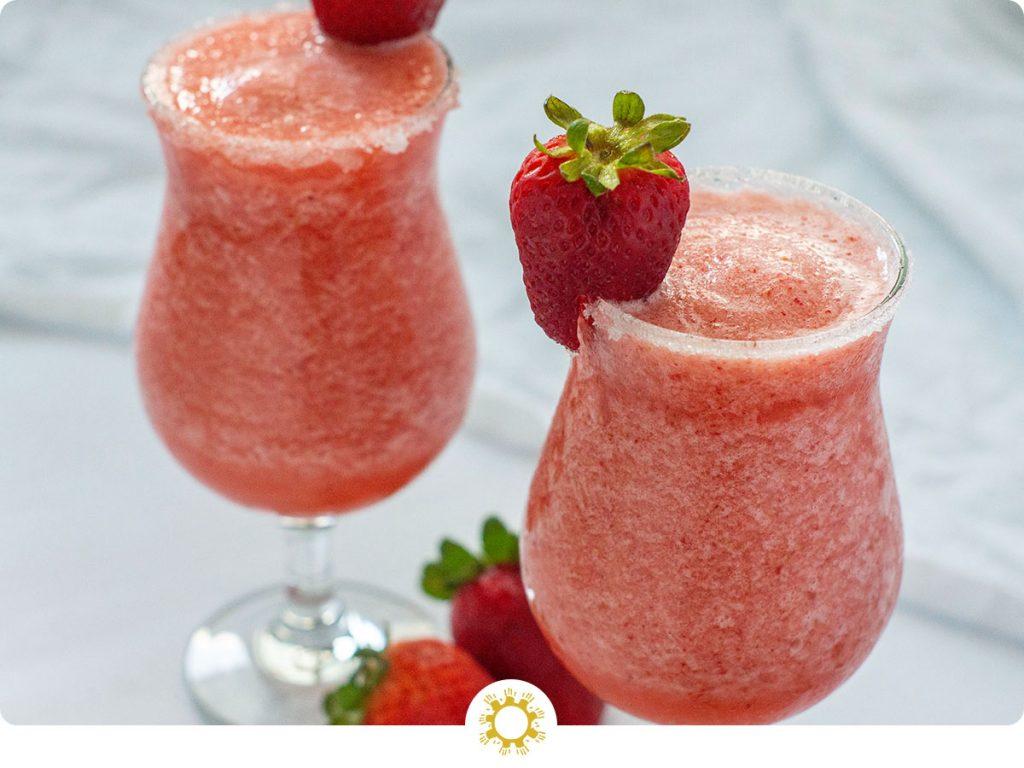 Strawberry Pineapple Daiquiri in glass with strawberry garnish (with logo overlay)