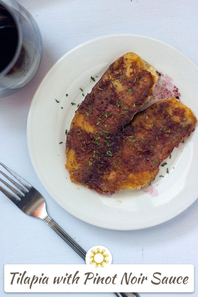 Tilapia with pinot noir sauce on a round white plate next to a fork and a glass of red wine on a white surface (vertical with title overlay)