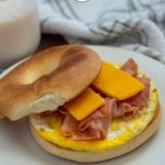 Breakfast bagel with egg, ham, and sliced cheese on a round white plate next to a glass of milk and a grey and white towel on a wooden surface (vertical with title overlay)