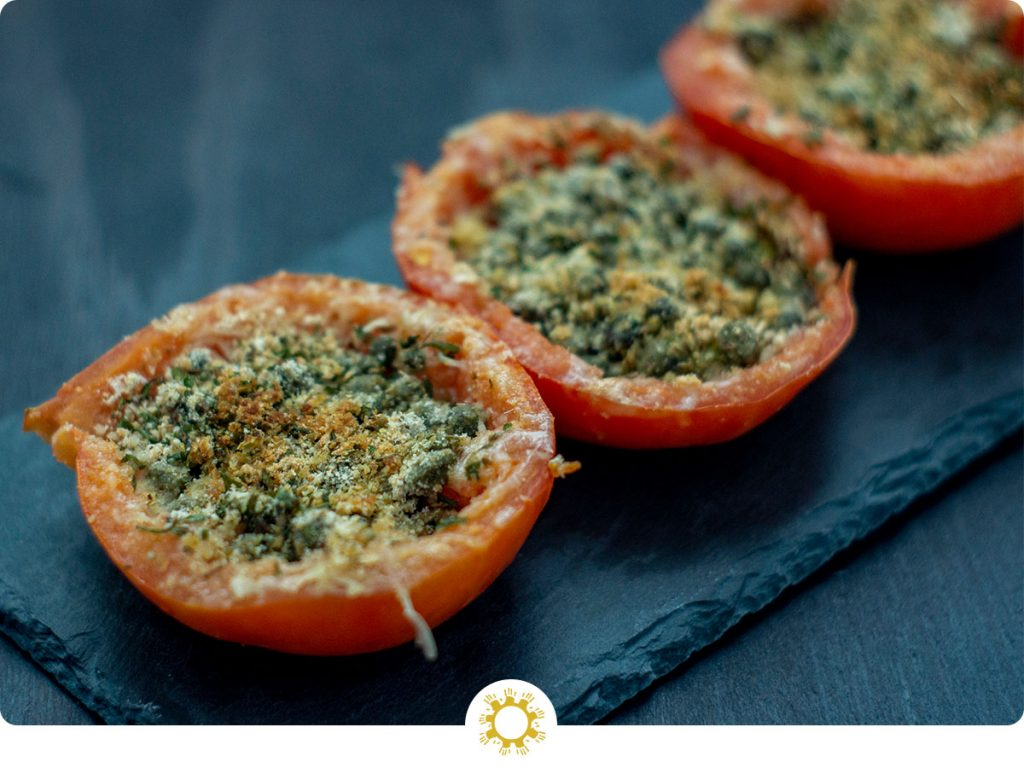 Three Cheesy Caper-Stuffed Tomatoes on a slate serving dish on a dark wooden surface (with logo overlay)