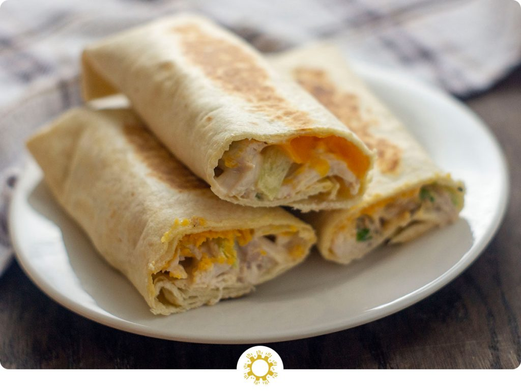 Side view of three crispy chicken wraps with the ends cut off to show the cheese and chicken mixture inside stacked on a small white round plate with a white and brown towel behind all on a wooden surface (with logo overlay)