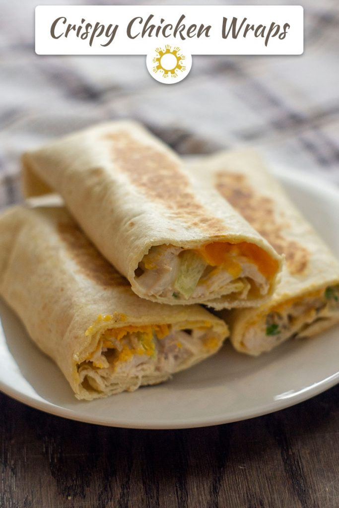 Side view of three crispy chicken wraps with the ends cut off to show the cheese and chicken mixture inside stacked on a small white round plate with a white and brown towel behind all on a wooden surface (vertical with title overlay)