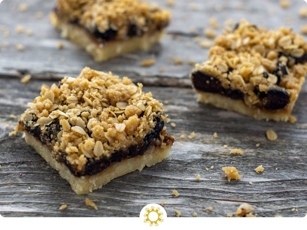 Three cut fig streusel bars on a wooden surface (with logo overlay)