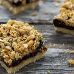 Three cut fig streusel bars on a wooden surface (vertical with title overlay)