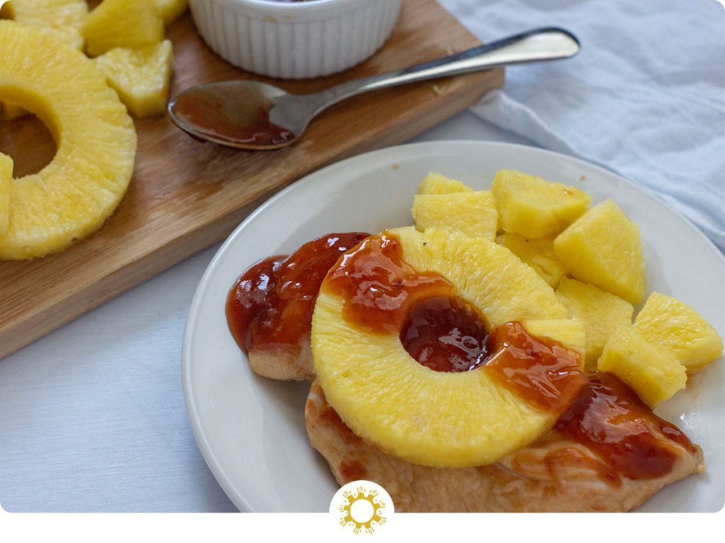 Chicken breast on a white plate covered with pineapple and sauce (with logo overlay)