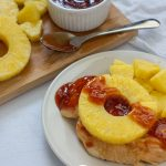 Chicken breast on a white plate covered with pineapple and sauce (with title overlay)