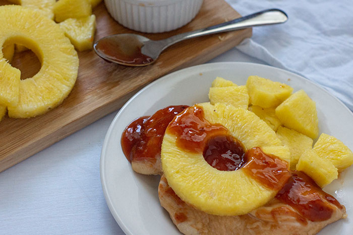 Chicken breast on a white plate covered with pineapple and sauce