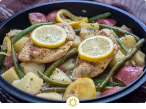 Cast-iron with diced tomatoes, lemon slices, green beans, and cooked chicken covered in seasonings on a brown towel (with logo overlay)