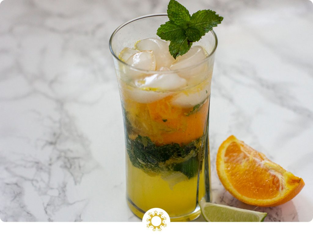 Orange mojito on a grey and white marbled background with slice of orange and lime with logo overlay