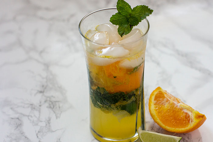 Orange mojito on a grey and white marbled background with slice of orange and lime
