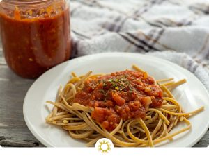 Spaghetti with homemade pasta sauce on a round white plate with a glass jar of pasta sauce behind next to a white and brown towel all on a wooden surface (with logo overlay)