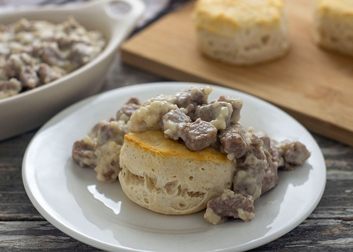Biscuit covered with sausage gravy on a round white plate with another biscuit on a bamboo board behind and more sausage gravy in a white oblong dish next to a white and brown towel all on a wooden surface