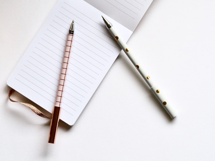 Two pens on top of a blank lined notepad ready to do a trash audit