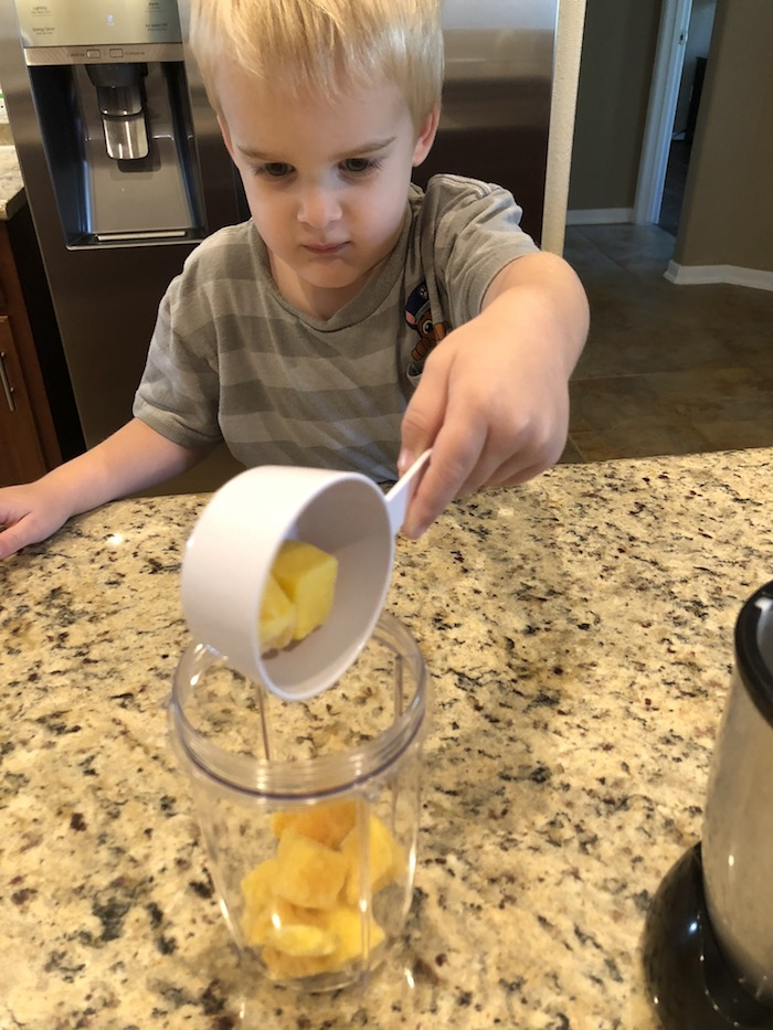 Young boy pouring ingredients into a blender cup