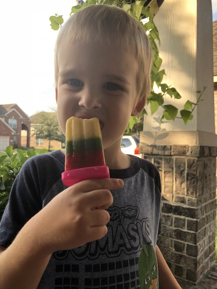 Young boy enjoying a tri-color ice pop