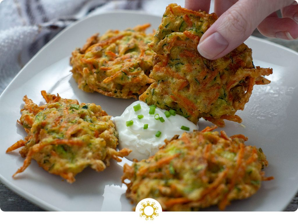 Woman's hand dipping a cooked vegetable fritter into sour cream in the middle of three other fritters on a square white plate with a white and brown towel behind all on a wooden surface (with logo overlay)