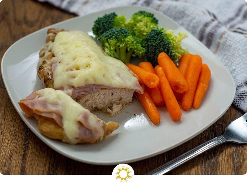 Cut piece of chicken cordon bleu with fresh carrots and broccoli on a square white plate with a stainless steel fork in front and a white and brown towel behind all on a wooden surface (with logo overlay)