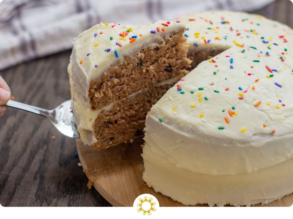 Serving spoon holding up a piece out of a double-layer chocolate cake with cream cheese frosting and rainbow sprinkles on a round bamboo platter with a white and brown towel behind all on a wooden surface (with logo overlay)