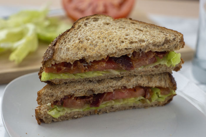 Classic BLT sandwich cut into triangles on a round white plate with a bamboo board topped with ingredients behind all on a white surface