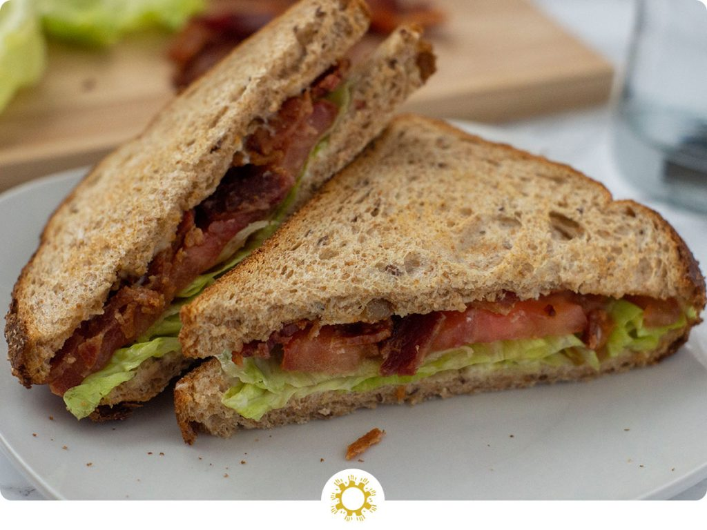 Classic BLT sandwich cut into triangles on a round white plate with a bamboo board topped with ingredients behind all on a white surface (with logo overlay)