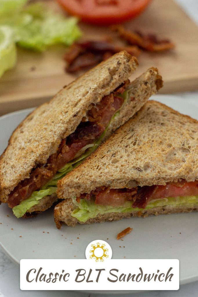 Classic BLT sandwich cut into triangles on a round white plate with a bamboo board topped with ingredients behind all on a white surface (vertical with title overlay)