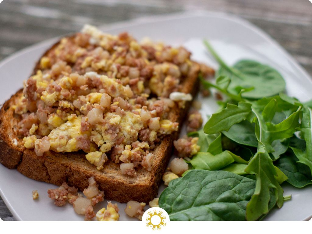 Corned beef hash breakfast toast: cooked corned beef hash mixed with scrambled eggs on a piece of toast next to spinach leaves on a white plate all on a wooden surface (with logo overlay)