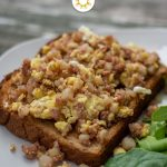 Corned beef hash breakfast toast: cooked corned beef hash mixed with scrambled eggs on a piece of toast next to spinach leaves on a white plate all on a wooden surface (vertical, with title overlay)
