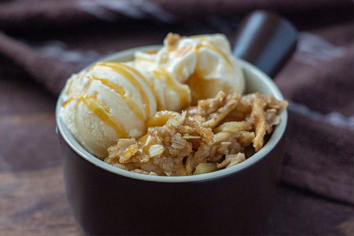 Brown dish filled with apple crisp topped with vanilla ice cream drizzled with caramel topping on a wooden surface